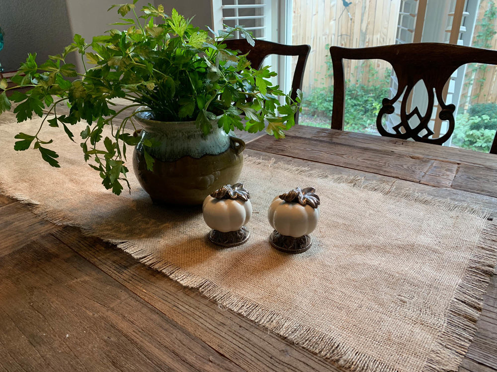 Rustic farmhouse table with burlap table runner and decorative plant and pumkins