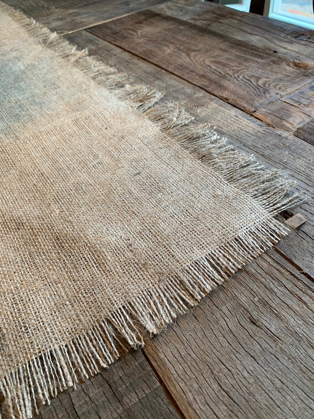 corner of fringed burlap table runner on rustic farmhouse wood table surface