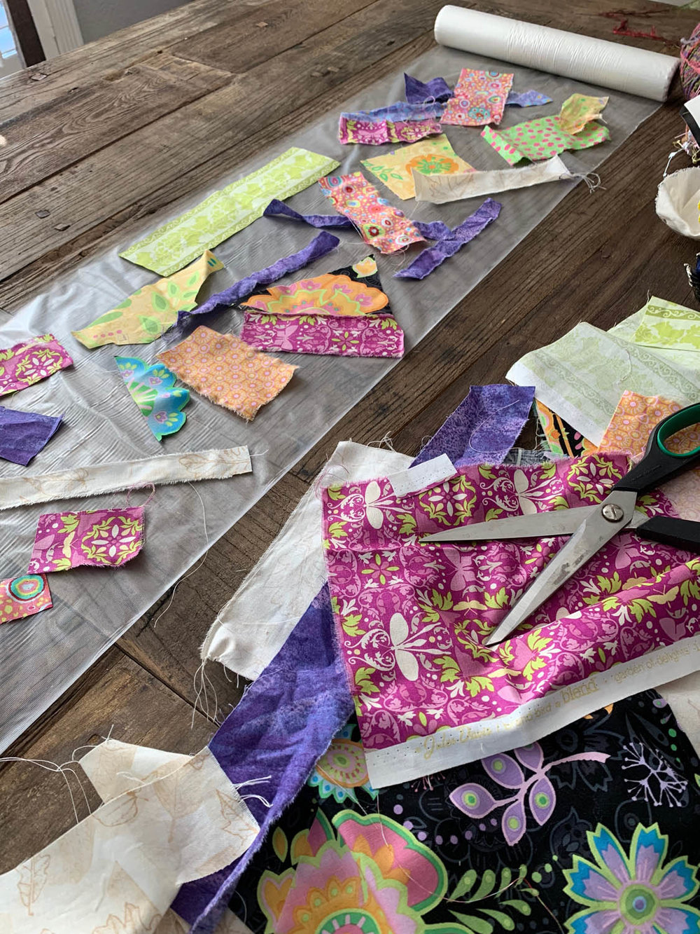 fabric scraps being laid on top of layer of Sulky Solvy stabilzer to create [Sulky Solvy] Upcycled Fiber Table Runner