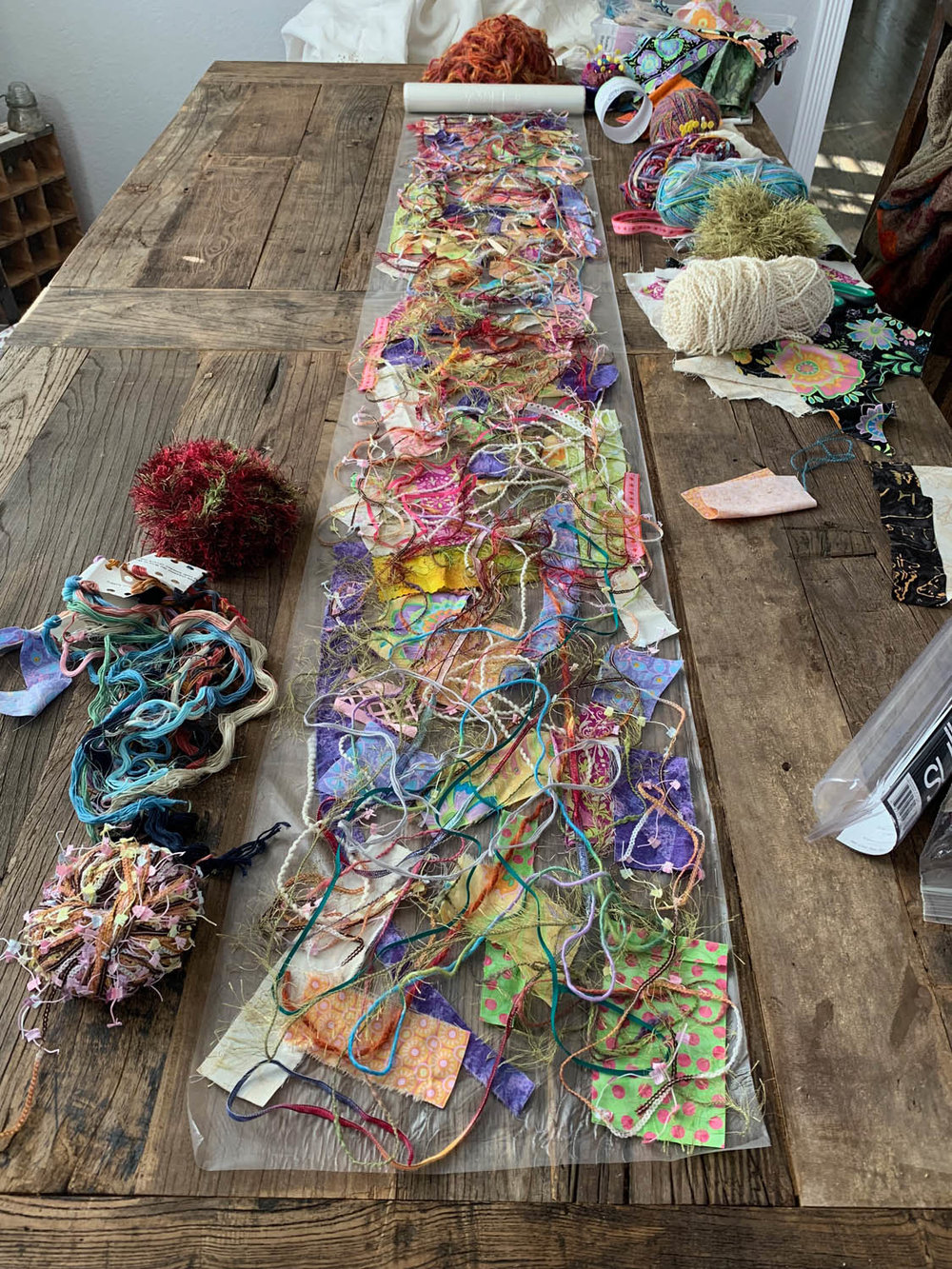 fiber and fabric scraps for table runner on first layer of Sulky Solvy before adding second layer of Sulky Solvy