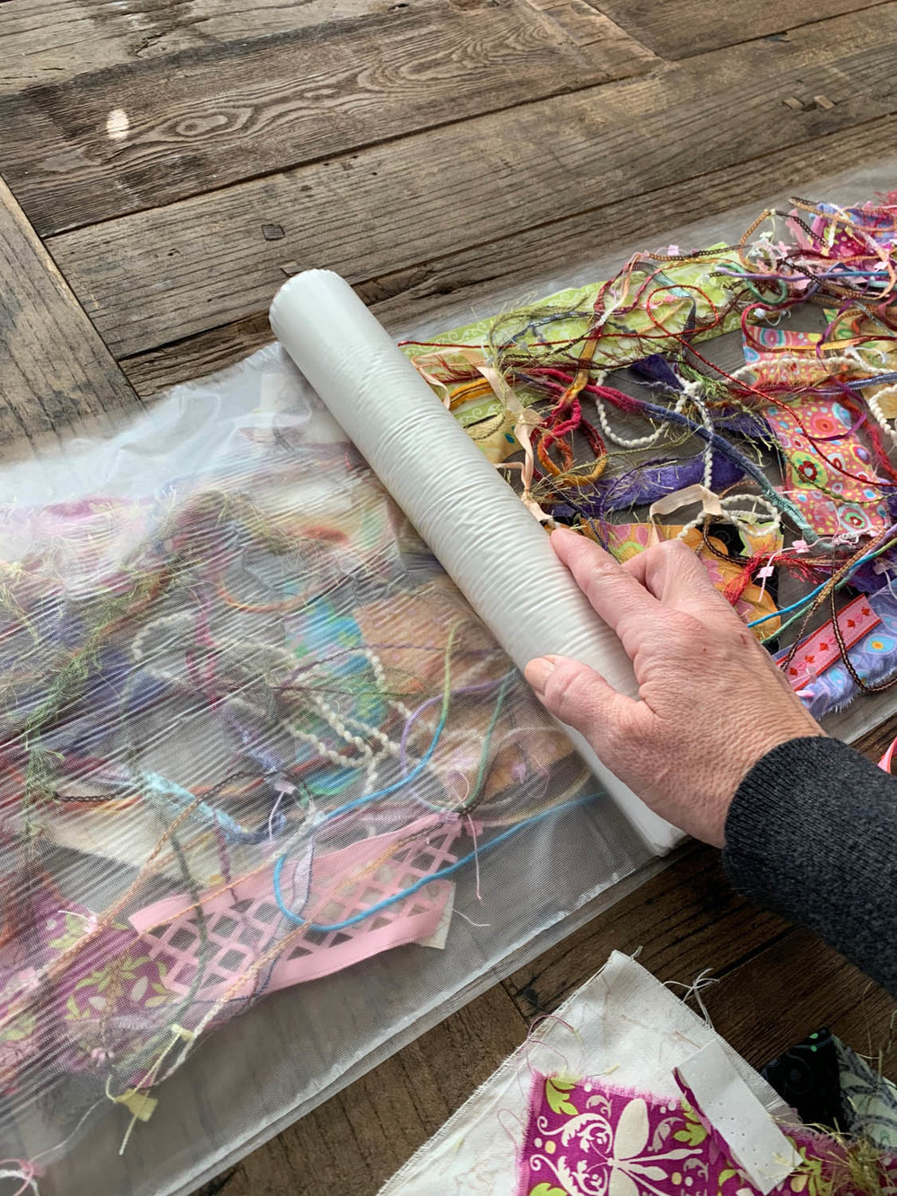 rolling top layer of Sulky Solvy over upcycled fiber bits for thread-quilted table runner