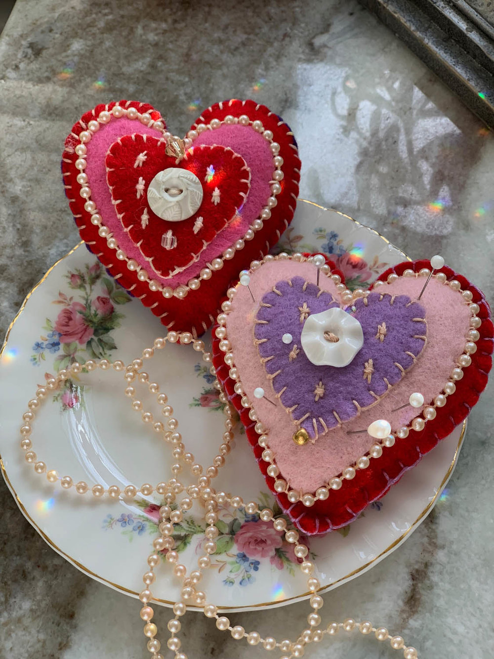Valentime ornament or pincushion with bead trim atop a floral china plate