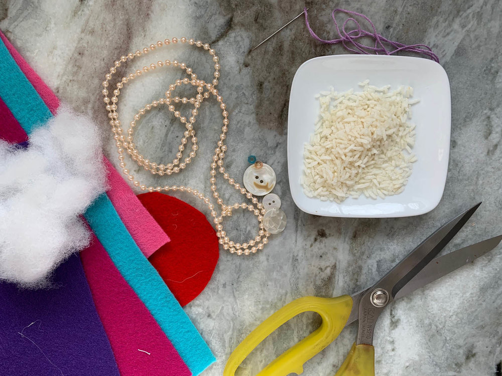 craft supplies fiberfill felt beat trim buttons scissors and dish of dry rice for filling