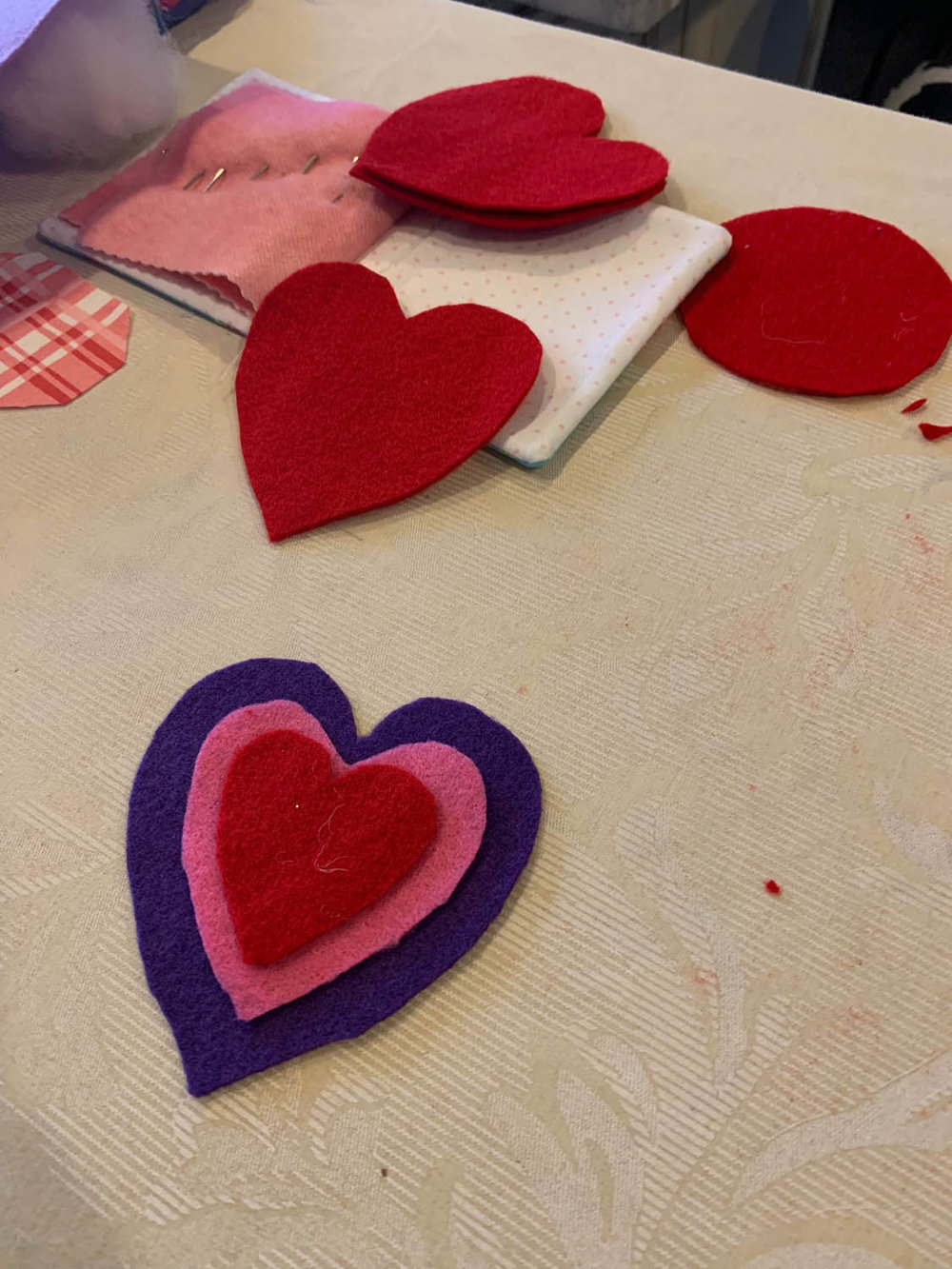 layered felt heart shapes in red pink and purple with a needlebook