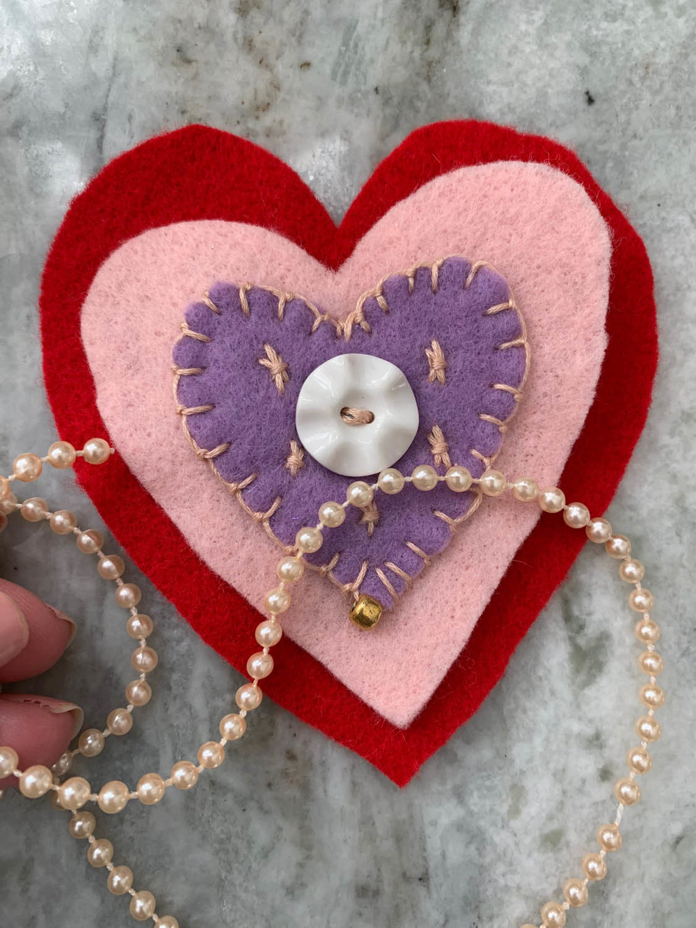 string of bead trim atop embroidered layers of felt hearts