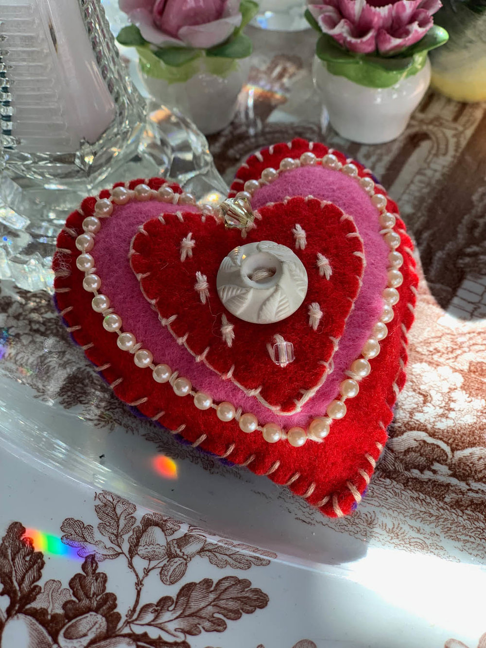 Finished Valentine ornament or pincushion made with embroidery and couched pearl trim on layers of pink and red felt stitched together and stuffed