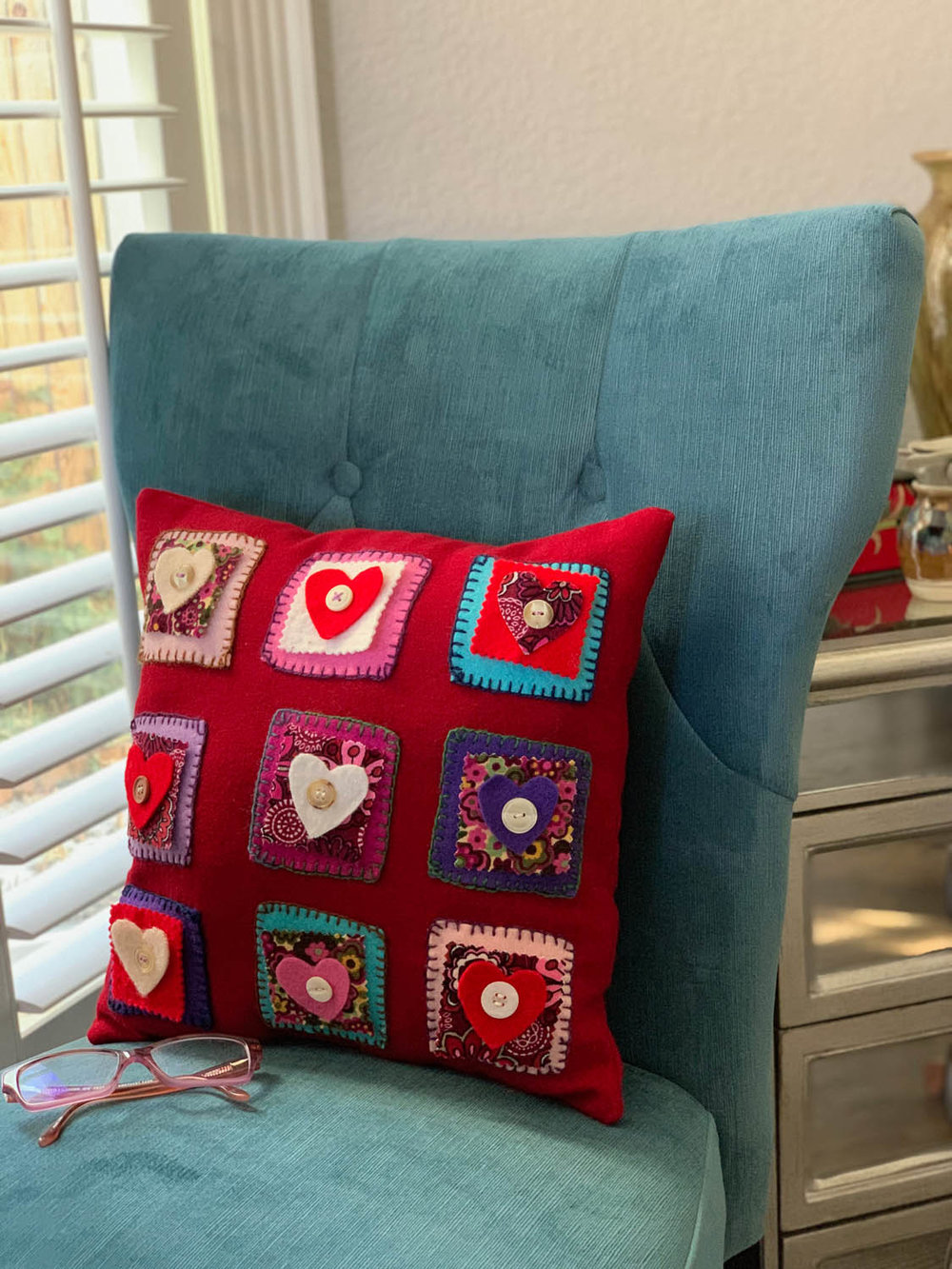Folksy Felted Valentine's Day hand embroidered nine-patch hearts pillow in red and vibrant colors.