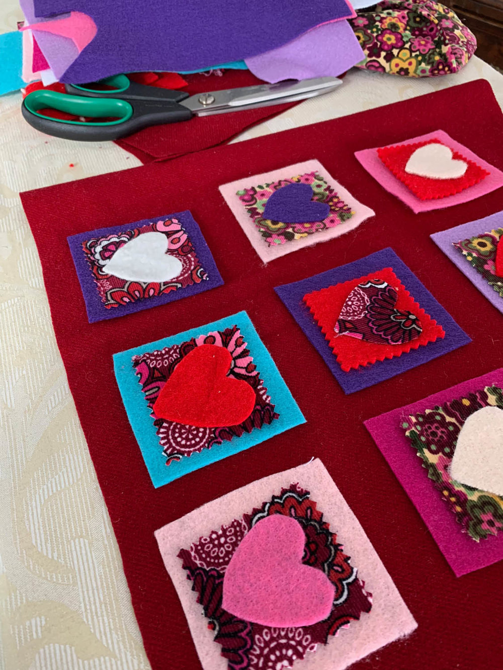 Auditioning felt heart shapes and fabric squares to make a DIY Valentine's Day pillow