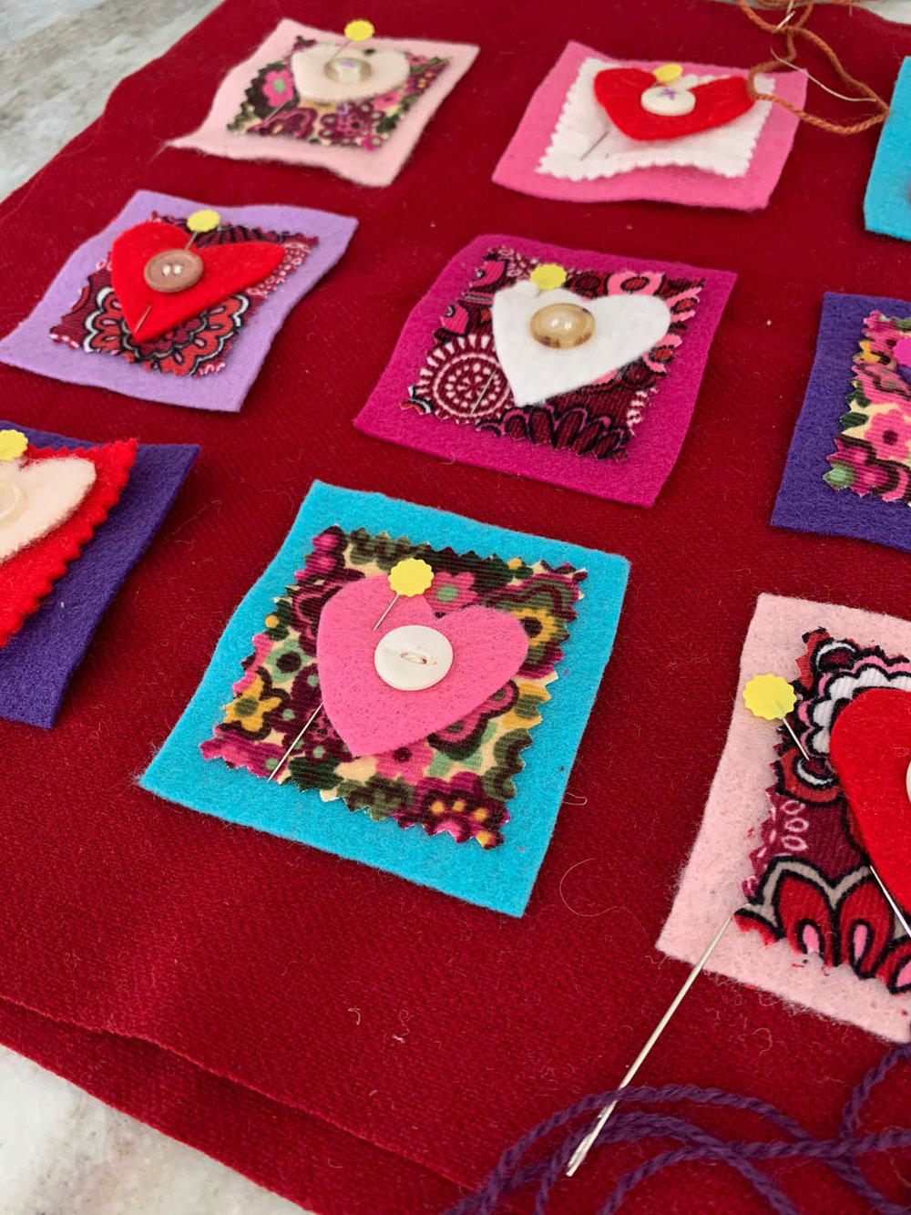 button trimmed felt hearts pinned to felt and fabric squares to make a nine-patch Valentine's Day pillow