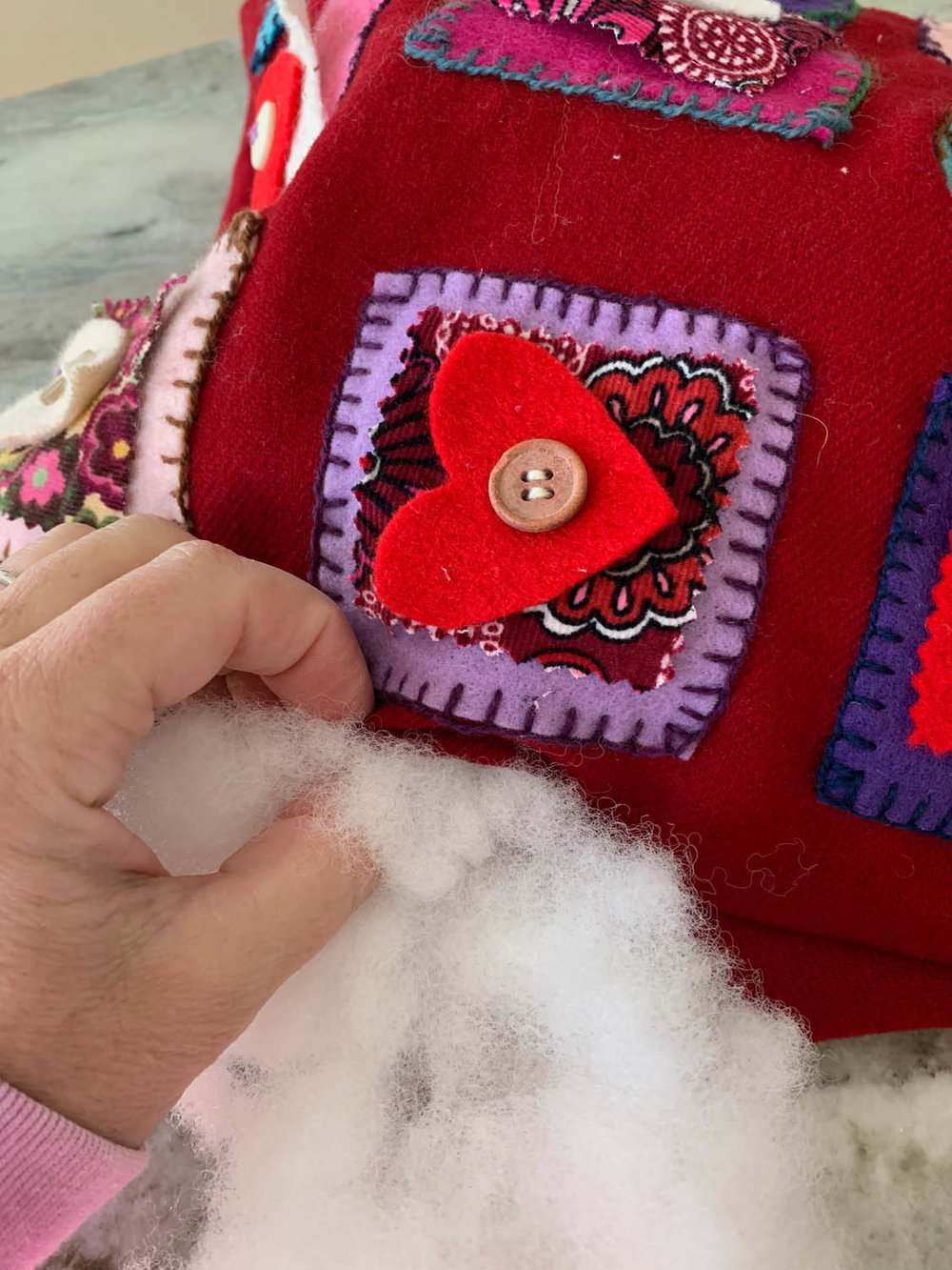 Hand stuffing fiberfill into folksy handmade felted heart pillow