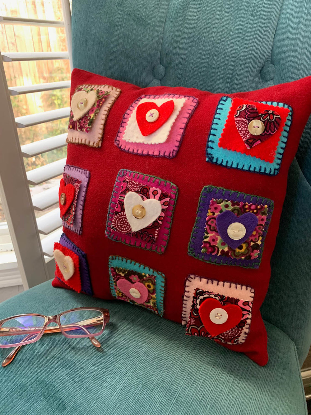 Finished Folksy Felted Valentine's Day heart pillow on a chair