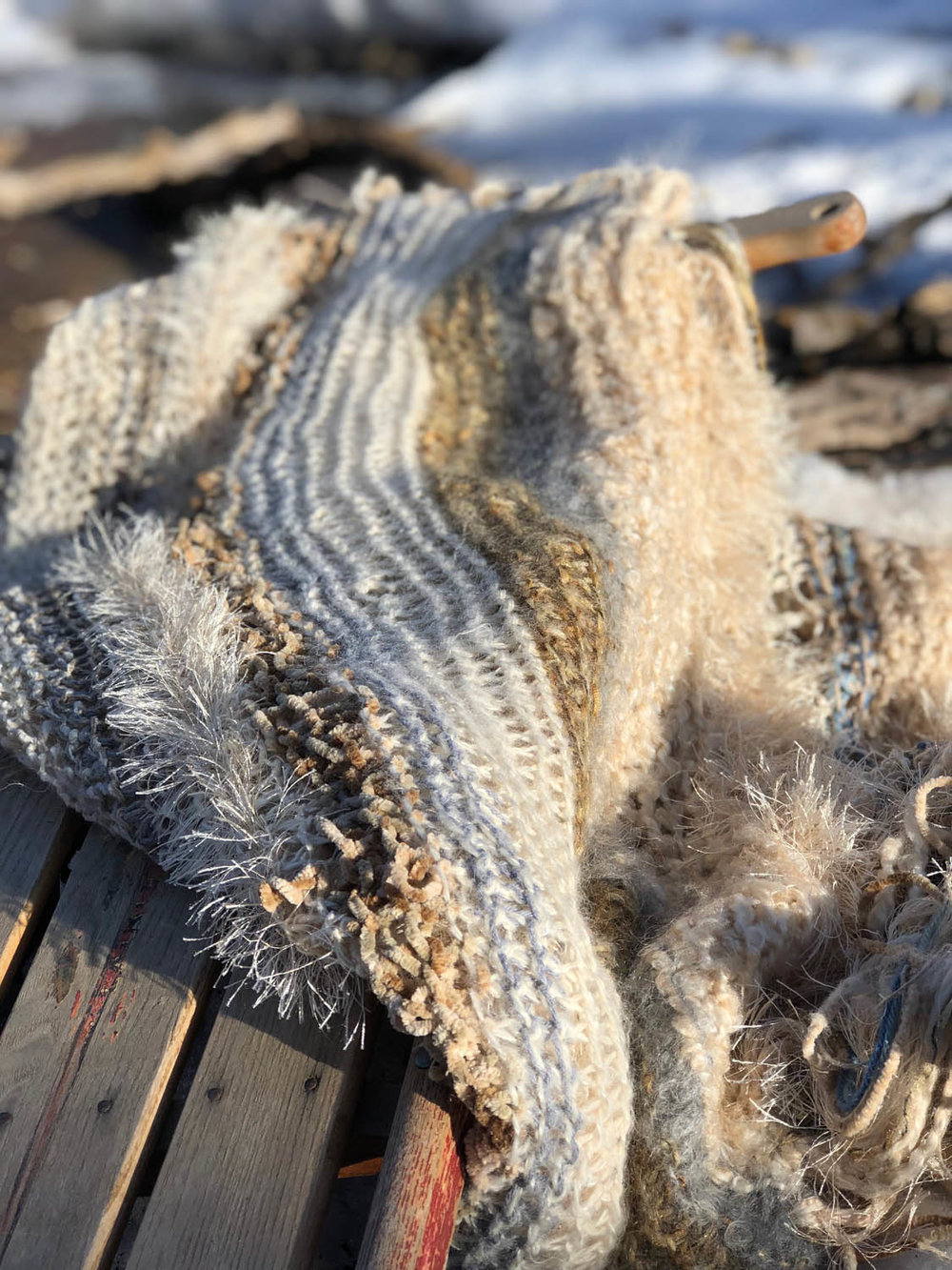 variety of scrap yarns in winter whites hand knit into a throw shawl