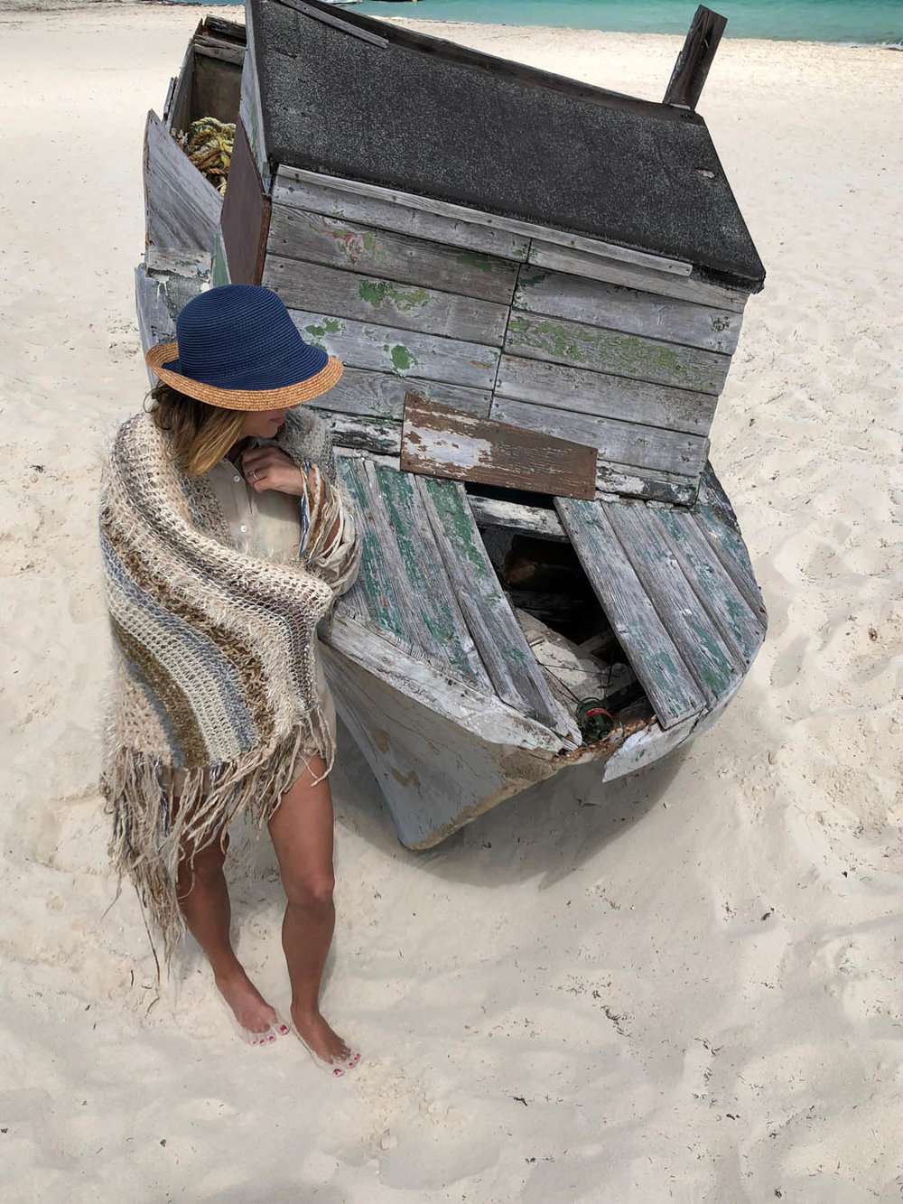 woman modeling a hand knitted winter whites shawl throw at a beach