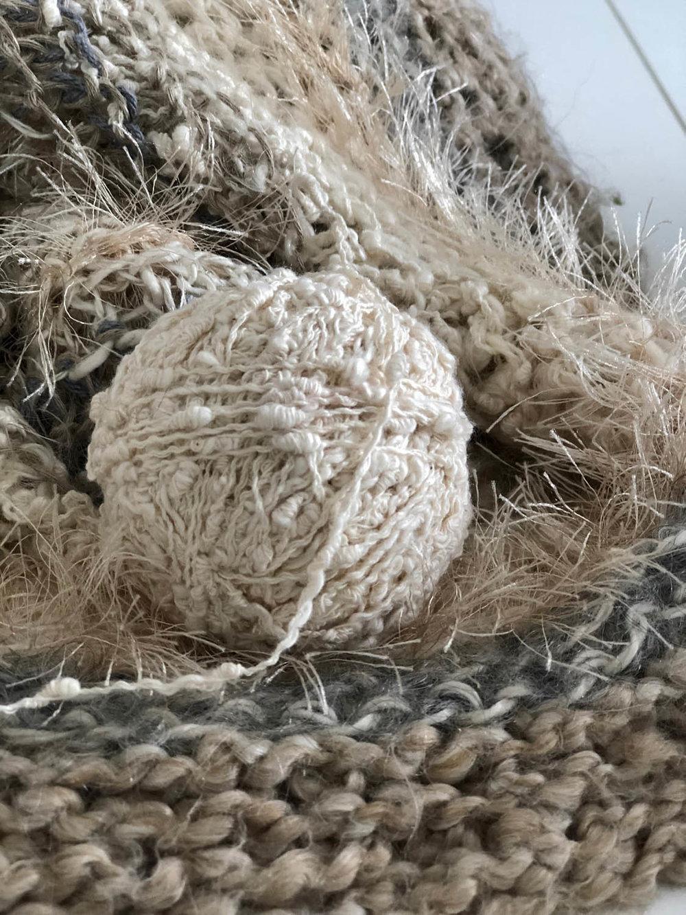 ball of slub yarn in white on hand knitted shawl throw