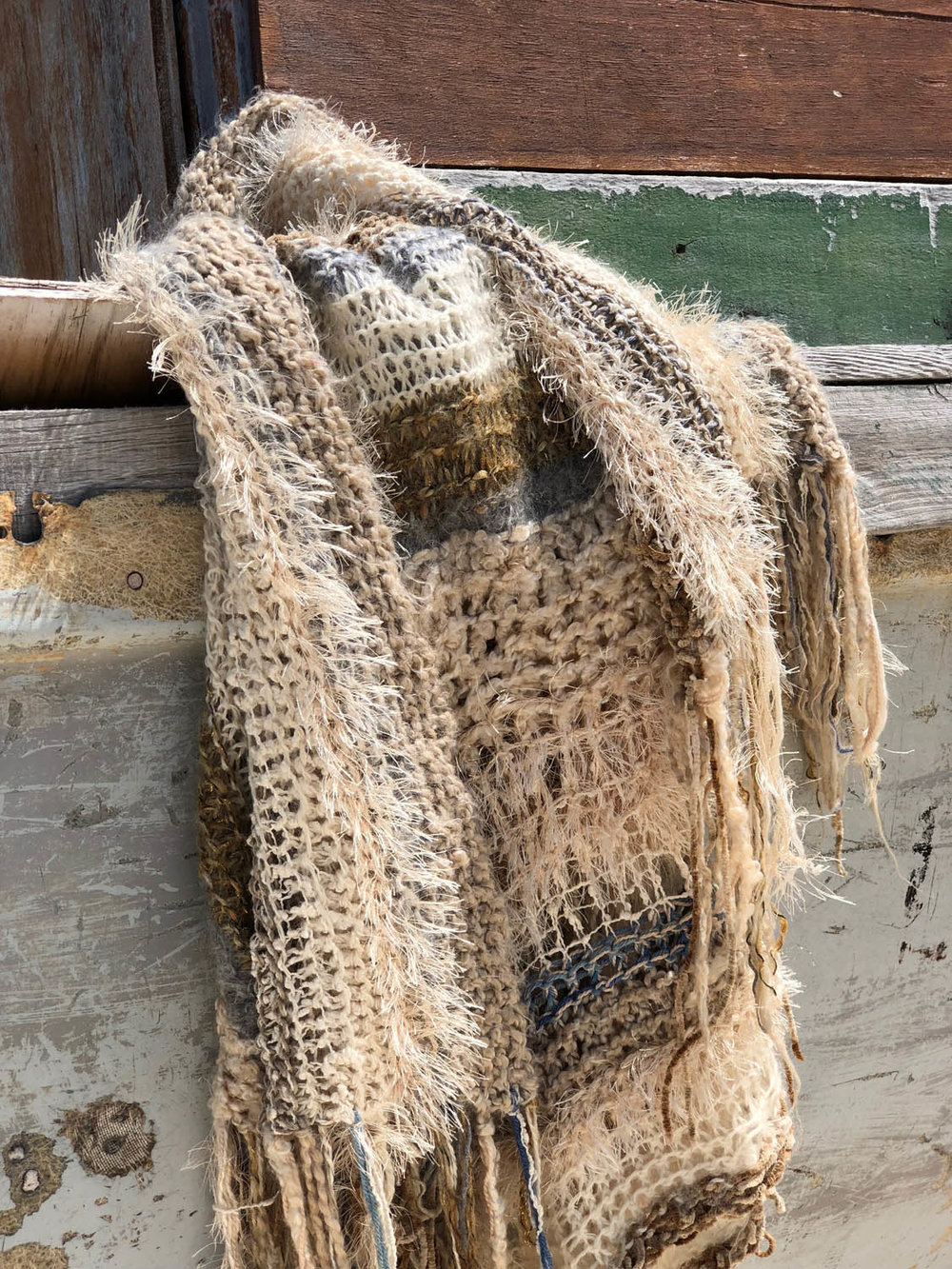 hand knit shawl throw in winter whites on wood planks