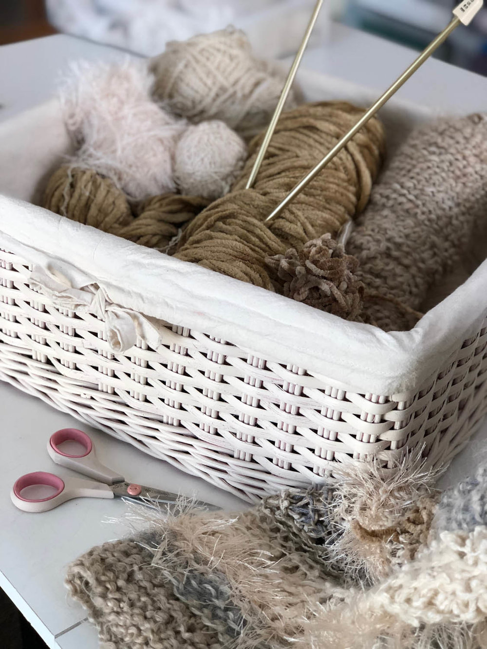 White wicker basket filled with variety of yarn balls in neutral winter whites with knitting needles