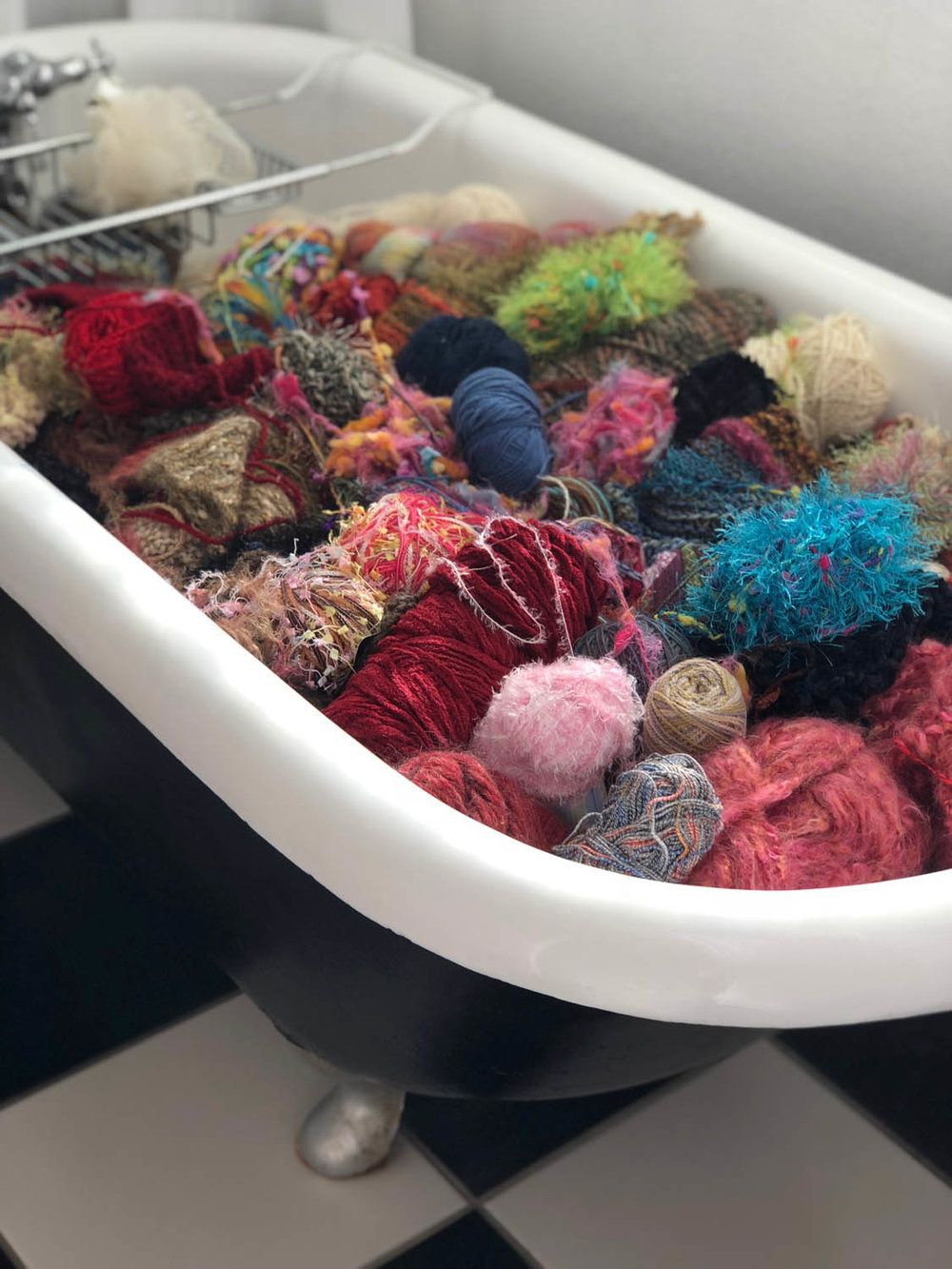 Claw-foot bath tub filled with colorful jewel toned balls of yarn