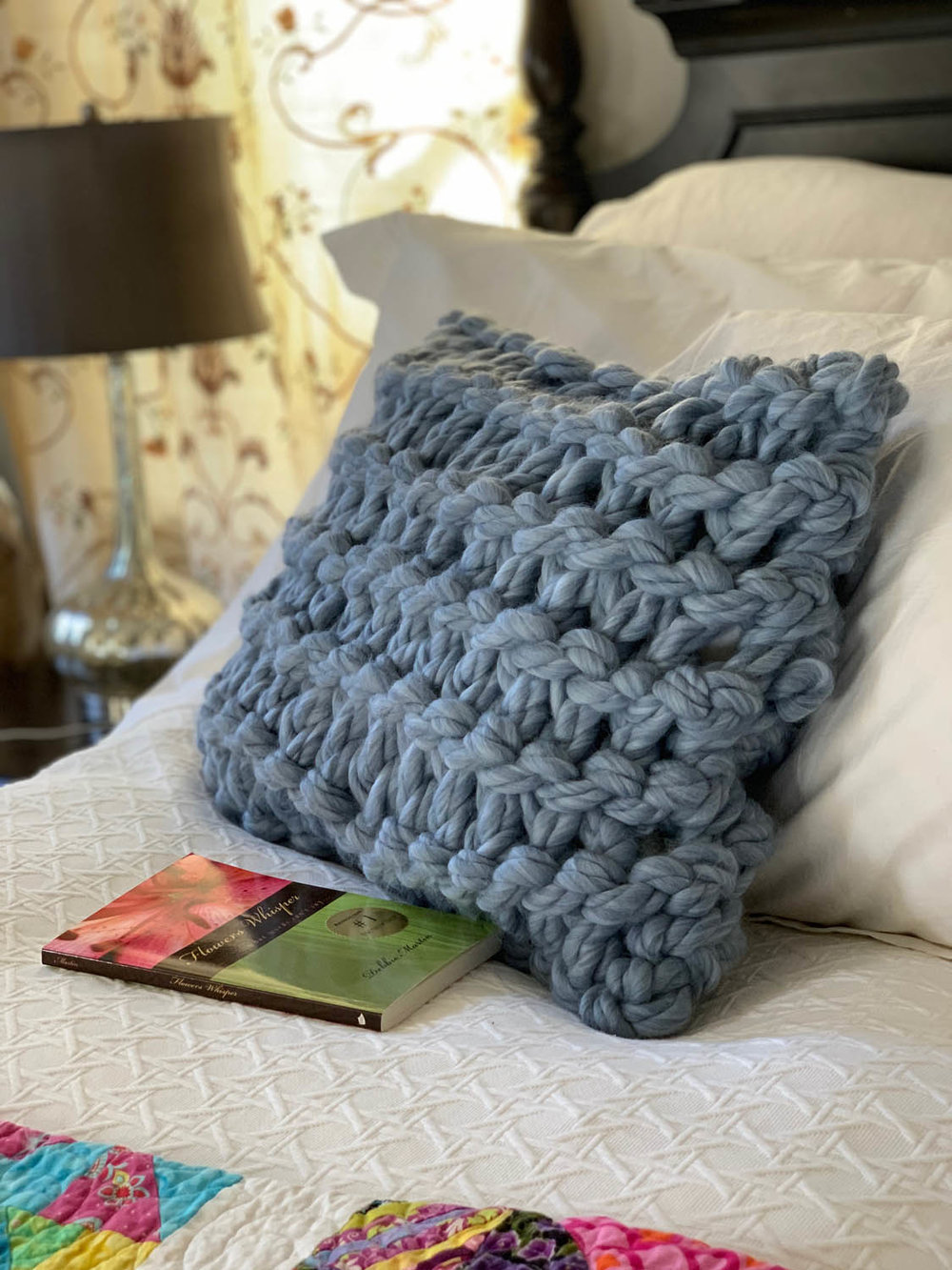 Jumbo Yarn Knit Garter-Stitched Pillow on a bed with quilt