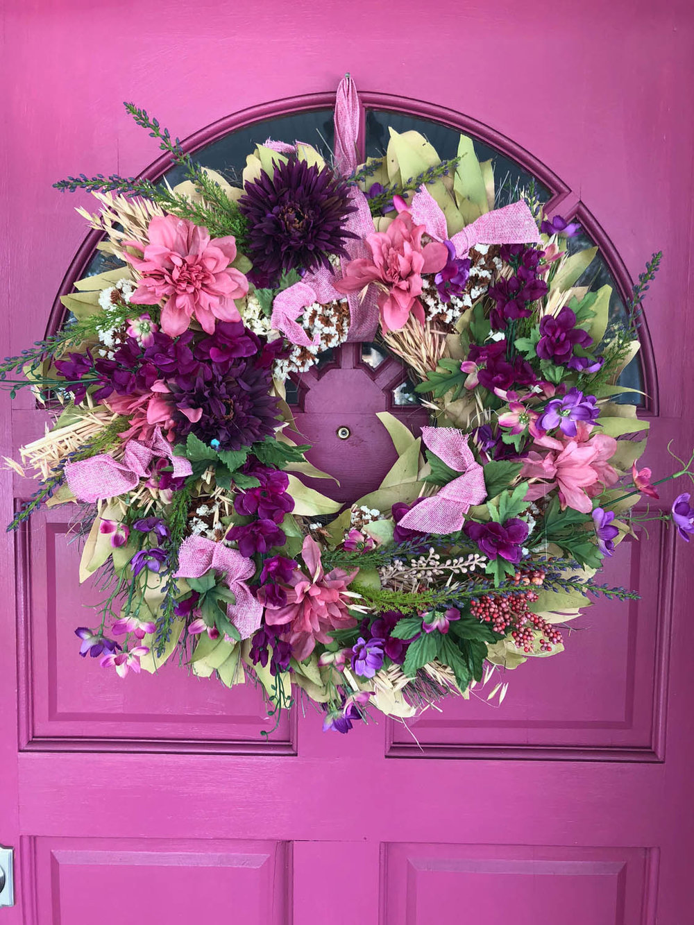 DIY spring wreath upcycle redo with fresh silk flowers hung on an exterior pink door
