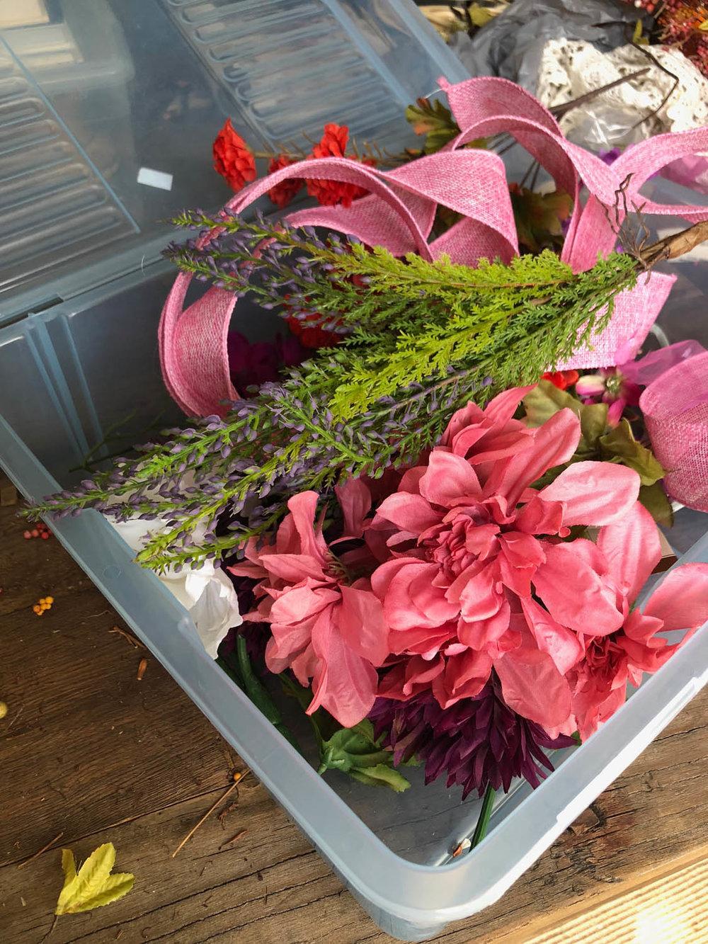 bin of silk flowers ribbons and greenery