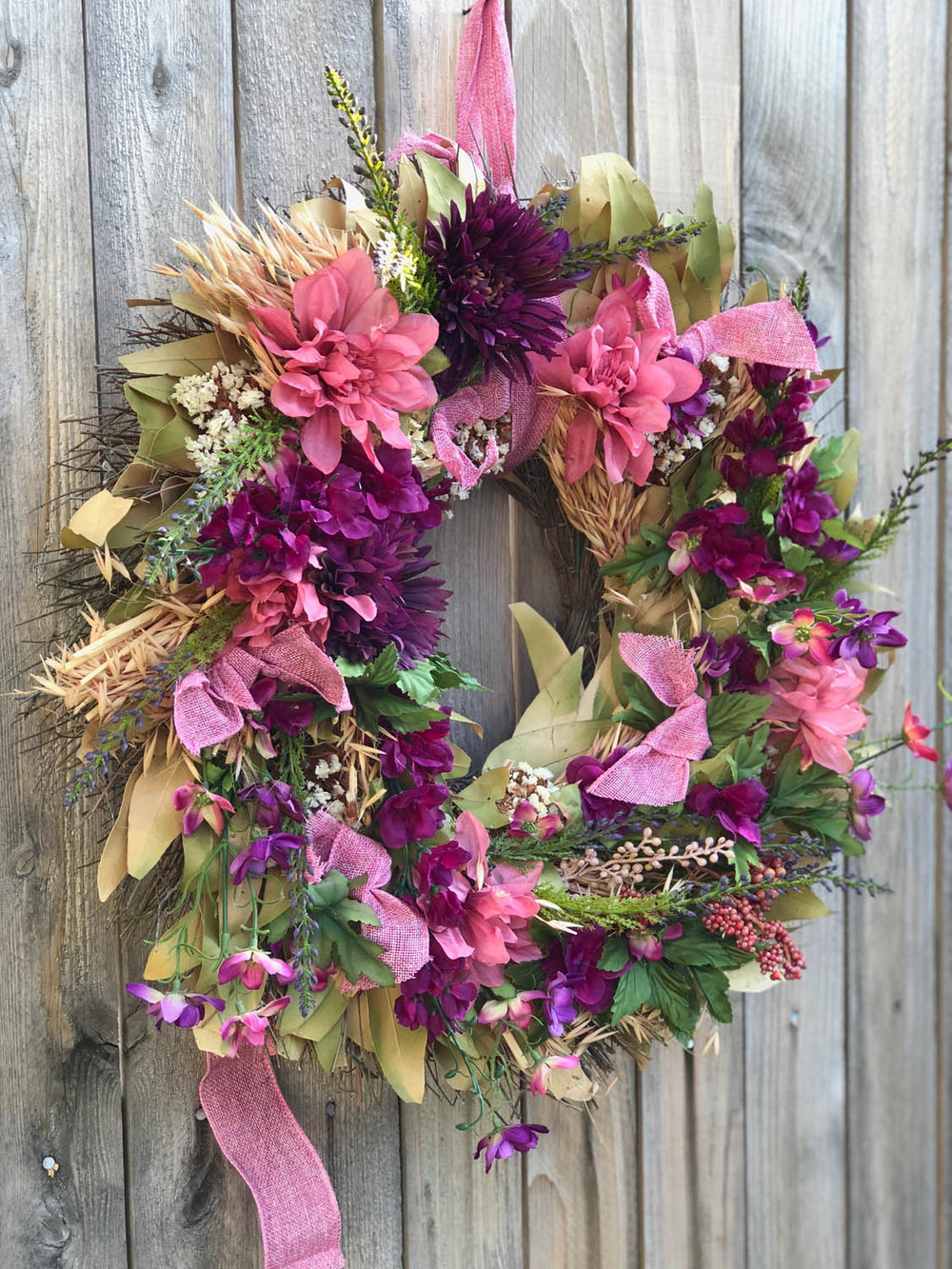 refreshed spring wreath hanging on exterior wood fence