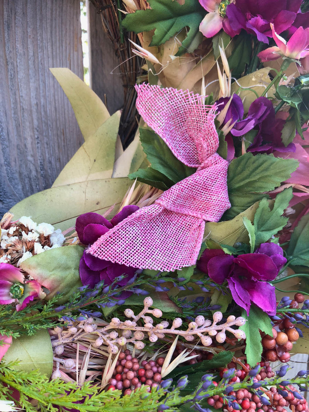 auditioning placement of ribbon on upcycled DIY wreath