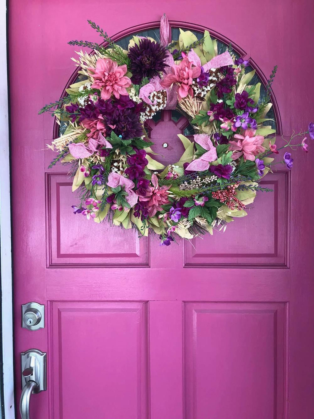 pink front door with spring floral wreath