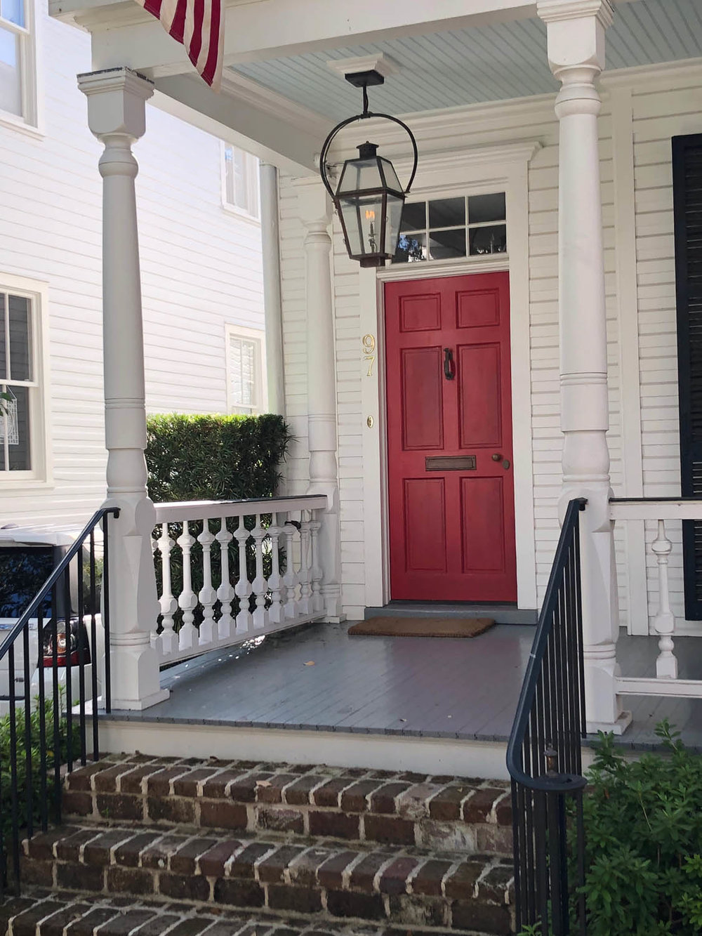 front porch with red door and white exterior paint
