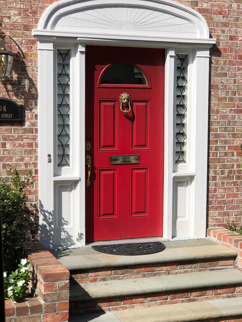 bright red door on brick home