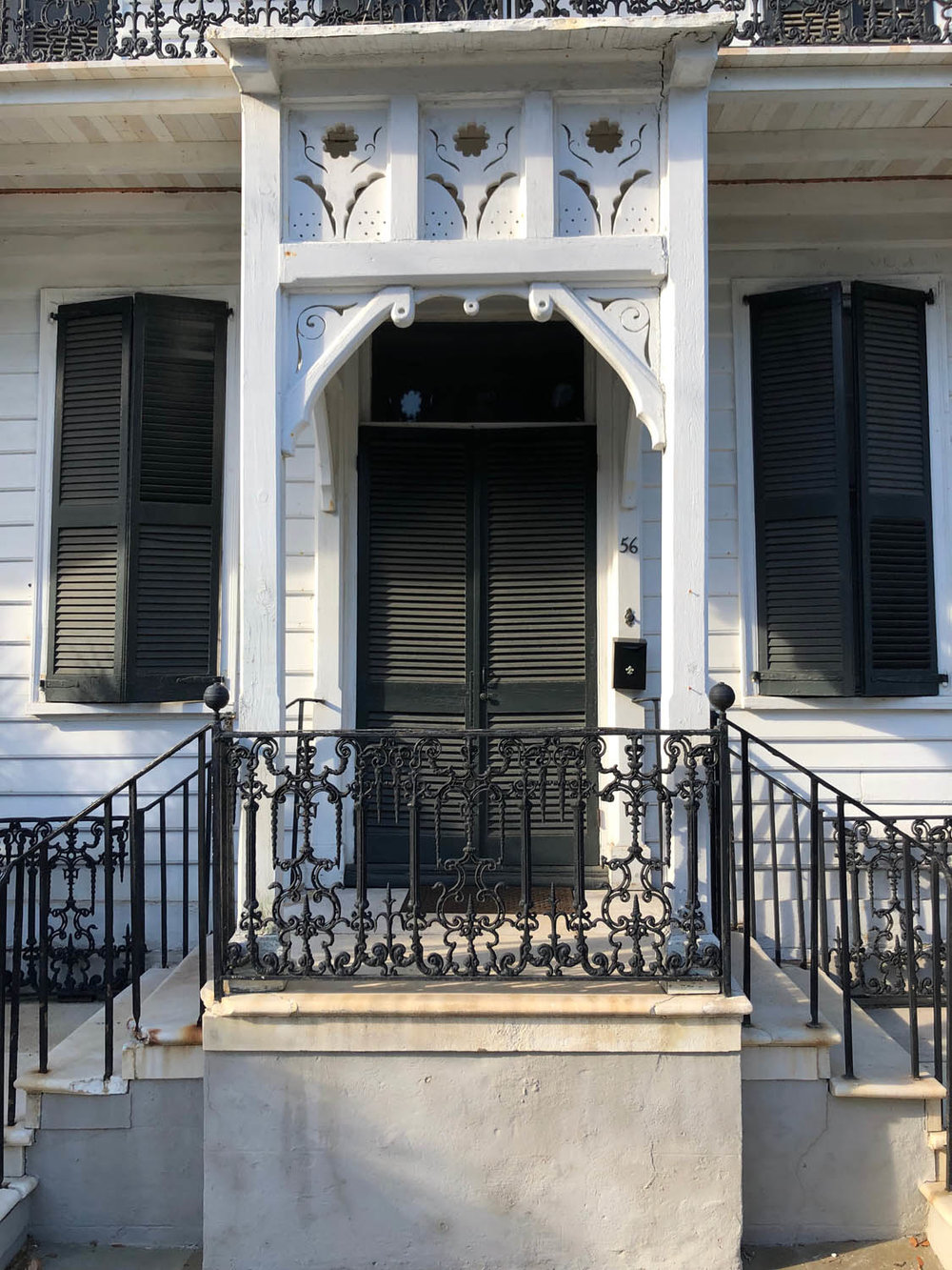 Grand white entrance with black louvered door of Charleston home