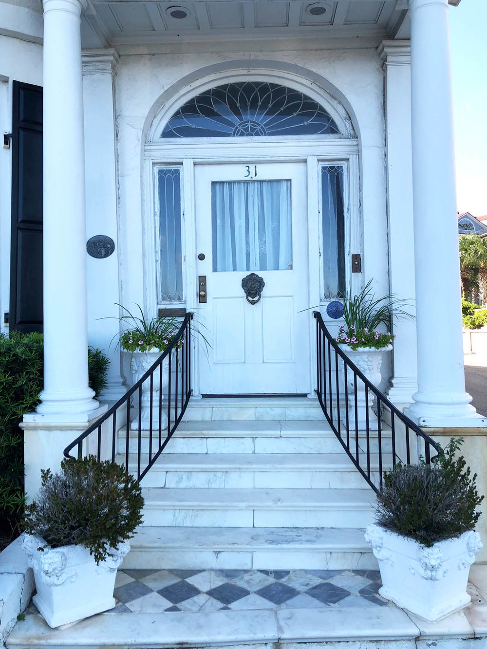 narrow Charleston house with a white door and white painted exterior