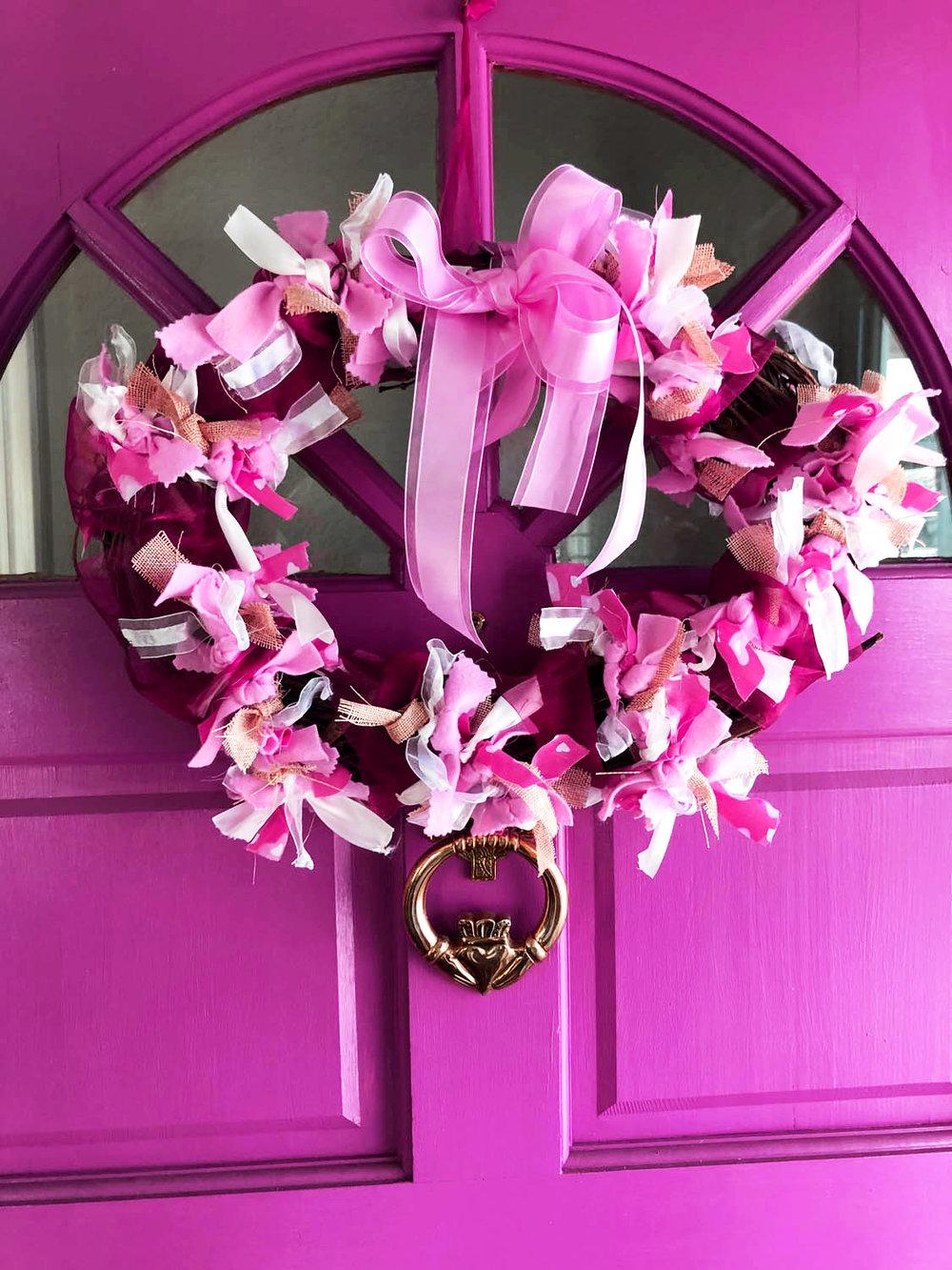 pink front door with heart-shaped valentine wreath