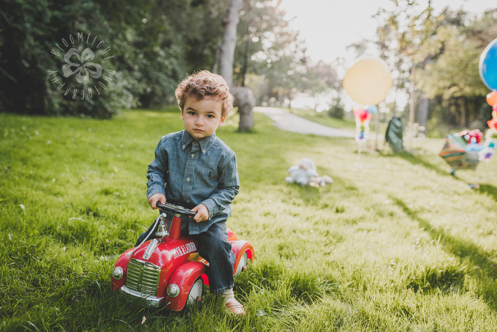 Two Year old baby boy wearing jeans and blue shirt driving his little red car toy in a beautiful summer day at a park in North York, Canada.