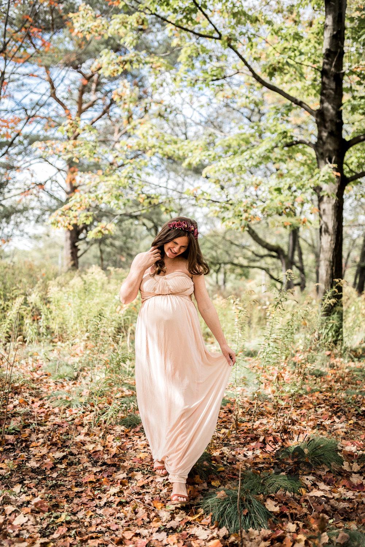 Beautiful mamma to be in a blush long dress walking in High Park in Fall season.