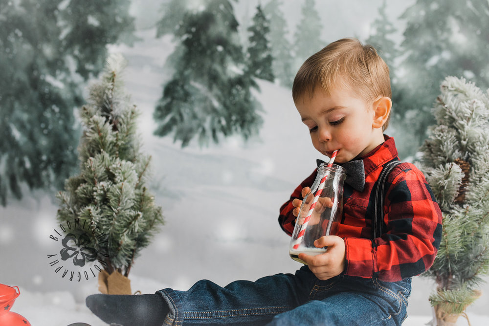 Cute baby toddler drinking milk in the Christmas mini session