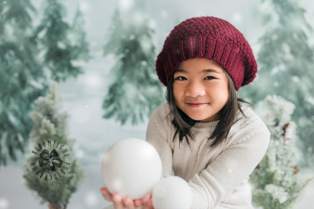 Lovely little girl holding snowball in her hands