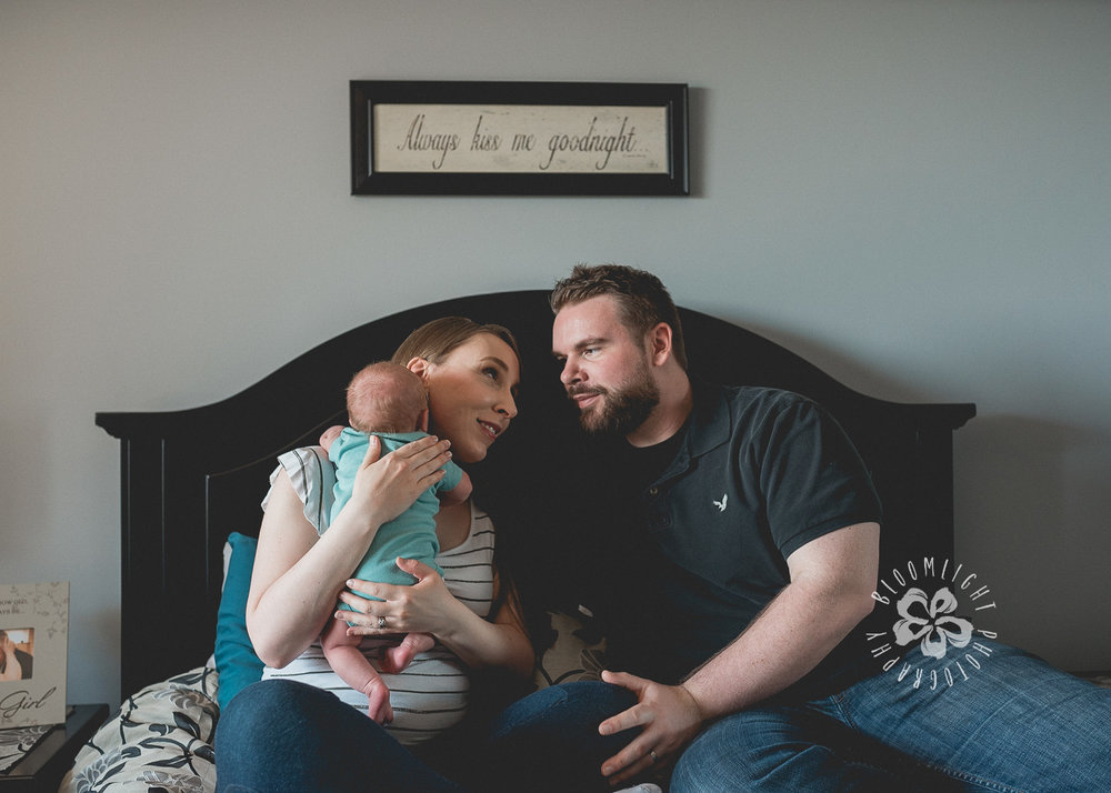 Image of family with newborn in their master bedroom