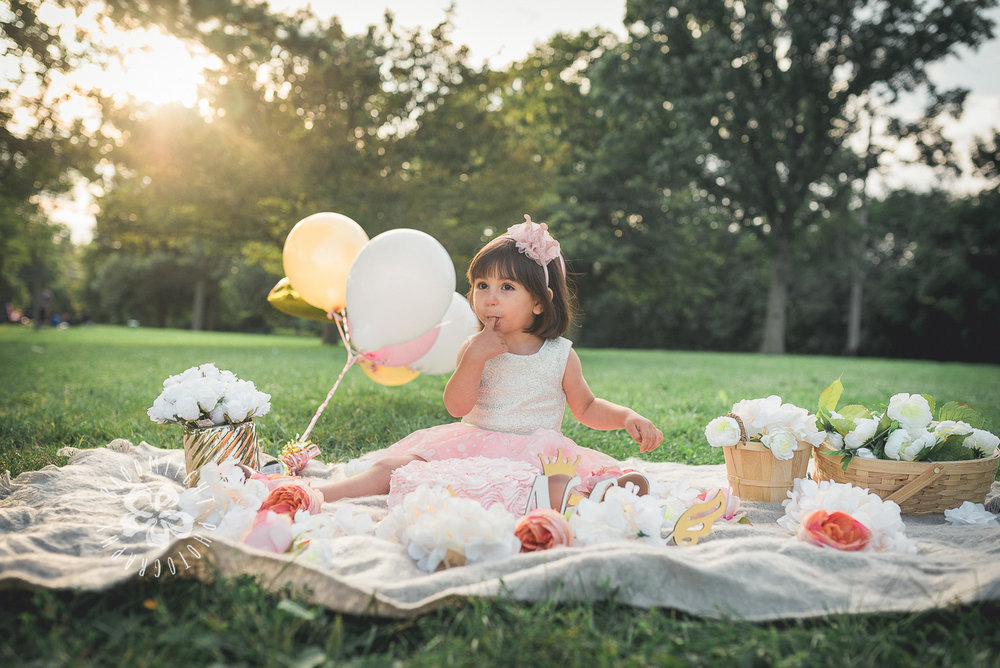 Picture of baby girl enjoying her second birthday cake while sitting on the grass in a park, North York