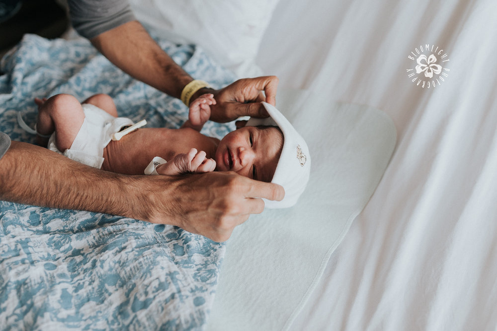 newborn getting dressed by his dad at a Toronto hospital photo session