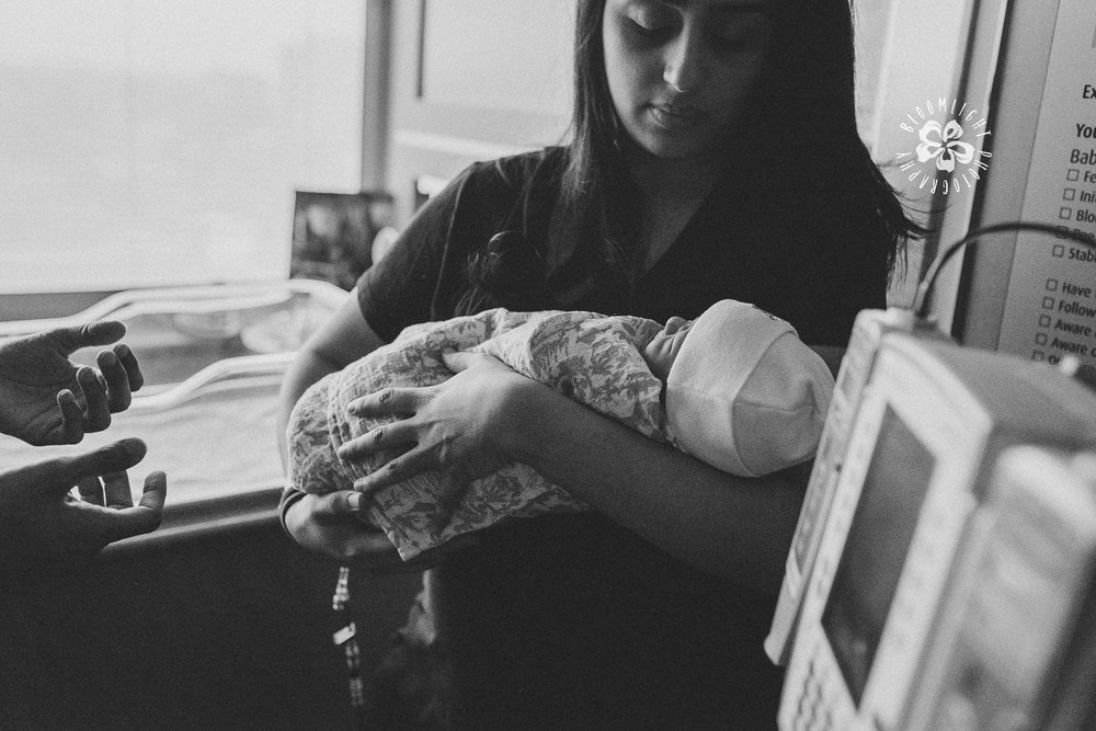 photo of a mom in black and white holding her newborn at a fresh 48 hour documentary photo session in Toronto.
