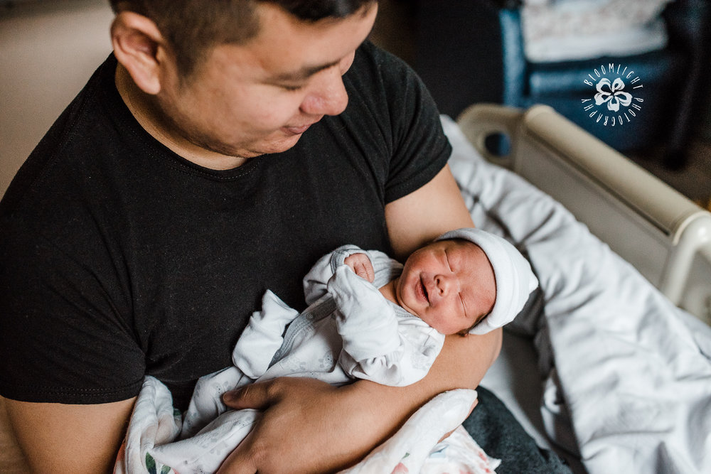 New dad smiling at his newborn 48 hours after birth in North York General Hospital