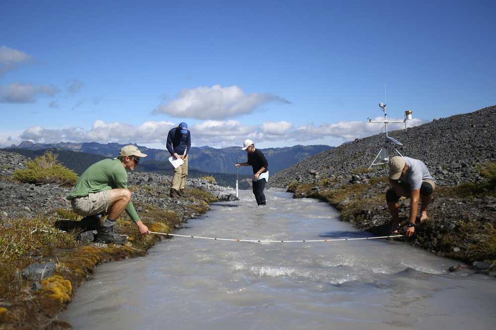 Erica Nied, center, makes her way across the icy runoff stream of Sholes Glacier to take depth measurements as Mauri Pelto records the data. Tyler Sullivan, right, and Ben Pelto, left, measure the width of the stream.