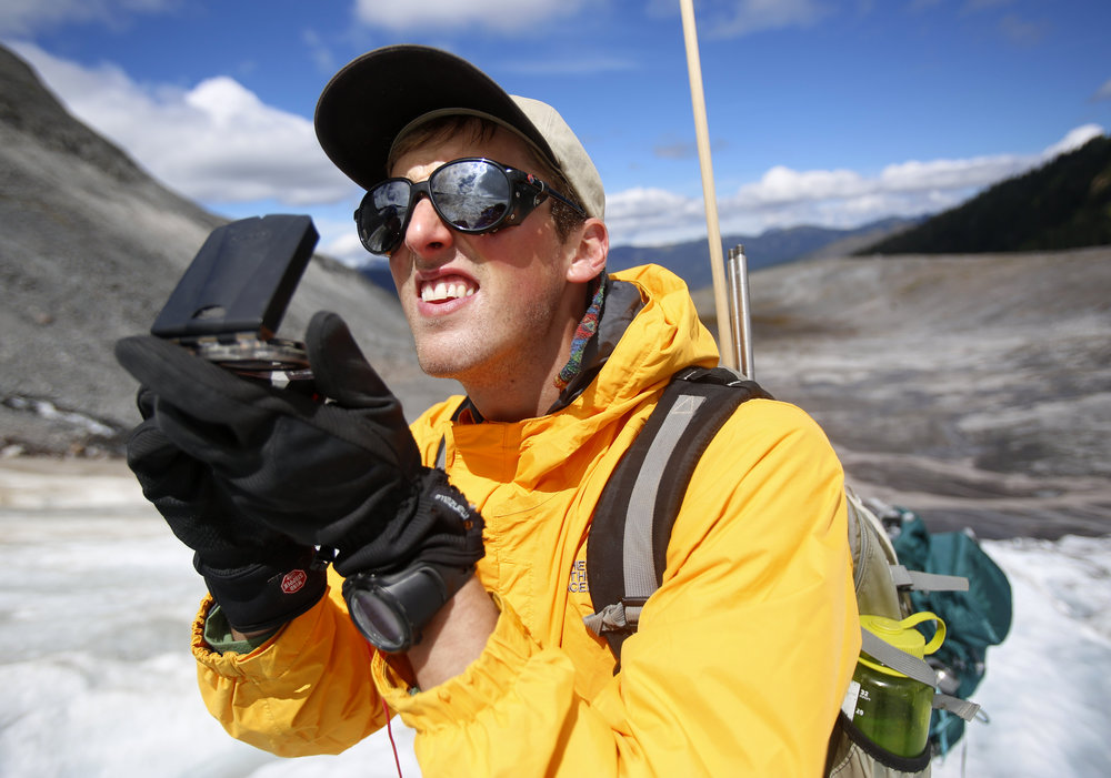 Ben Pelto, son of Mauri Pelto, uses a compass to map the size of Sholes Glacier.