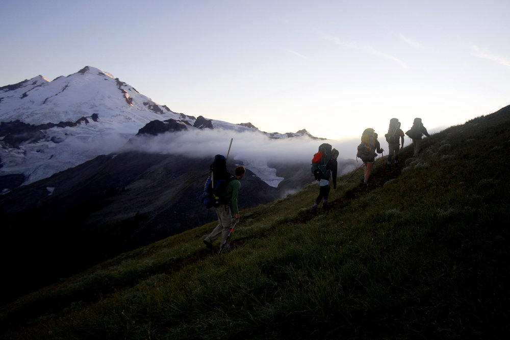 The research team heads toward a campsite as Mount Baker catches the last of the day's light on Thursday, Aug. 6, 2015. This is Pelto's 32nd year collecting data on Sholes Glacier.