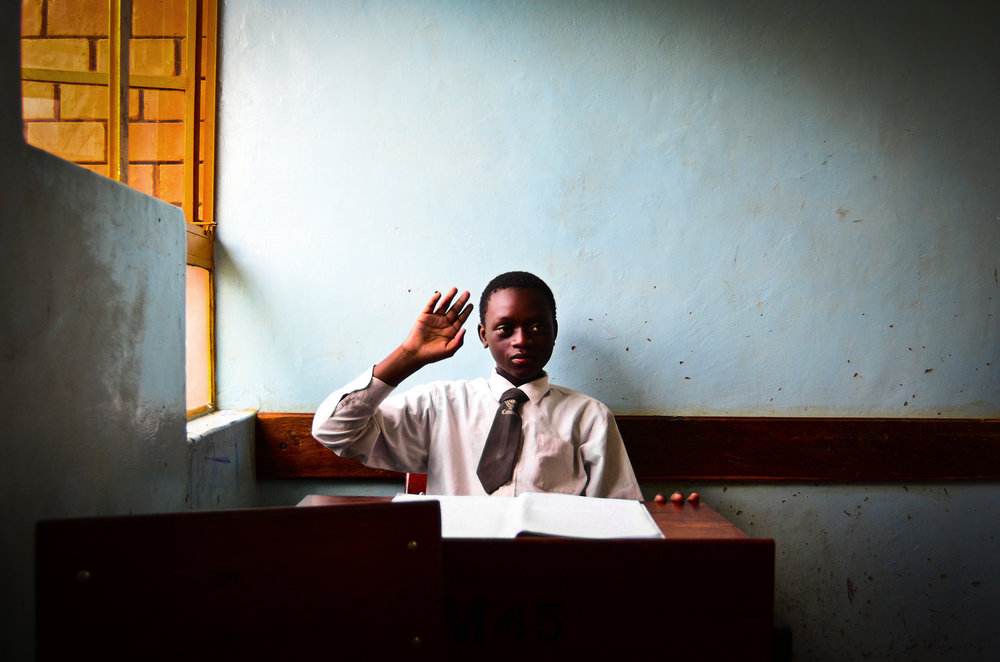 Ron Chihula, 14, raises his hand during class at the Chikuni Mission in Zambia, Africa, Thursday, March 17, 2011. The Jesuit mission hosts over 700 male students, and priests teach the classes as well as lead mandatory daily mass. (Sy Bean/Seattle University)