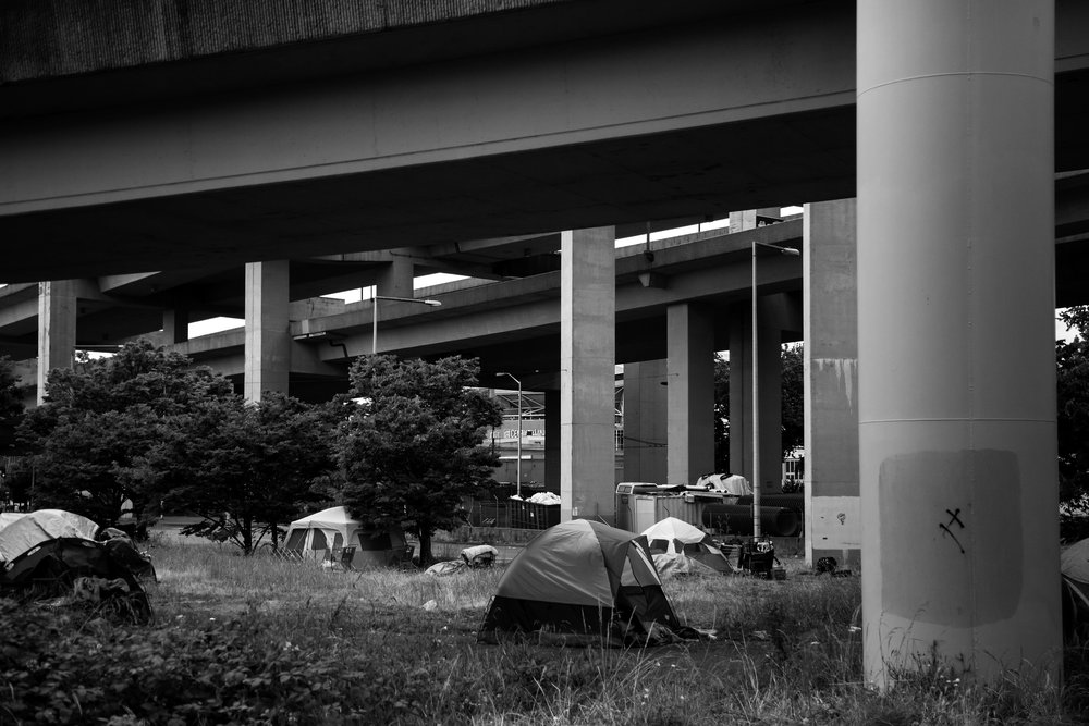 Over a dozen tents sit underneath Interstate 90 near the intersection of Airport Way South and South Royal Brougham Way, which is located near the Jungle, Friday, May 27, 2016.