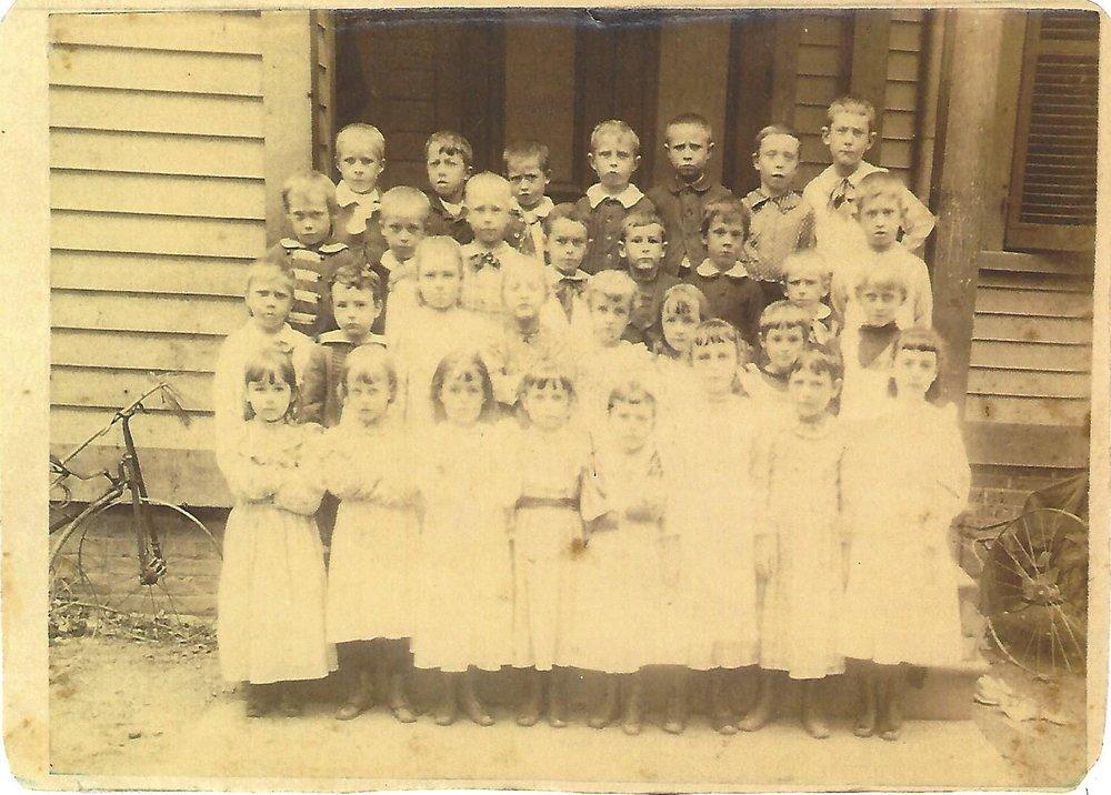 Children pose in front of the Grand Avenue School circ 1893