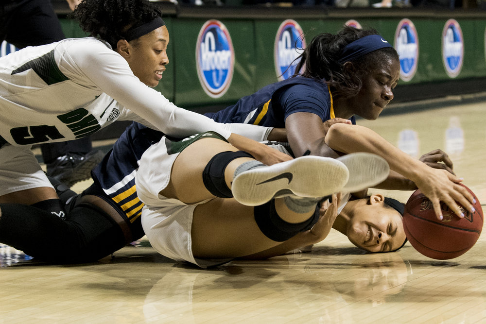 Quiera Lampkins, Mikaela Boyd, and Amani Burke struggle for the ball, causing Amani to hit her head while Ohio University plays University Of Toledo in Athens, Ohio.