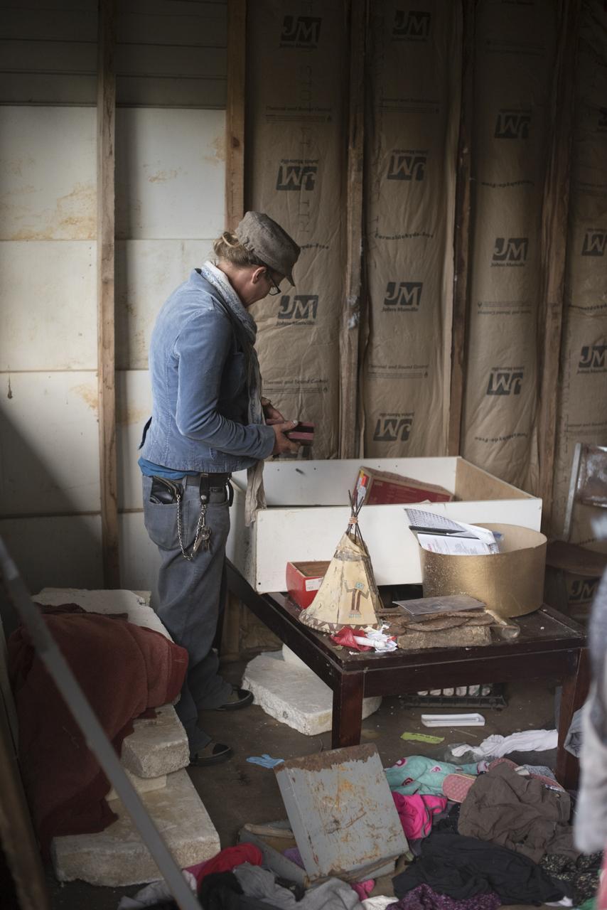 Trina Mcafee rummages through belongings in her house.