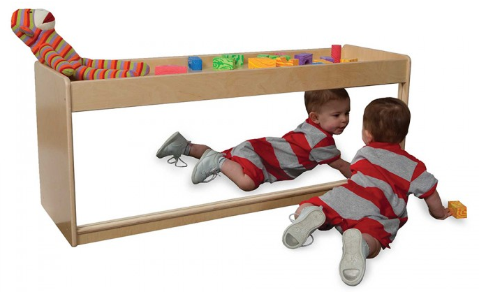 The  Infant Pull-Up Storage  serves as an infant pull-up, shelf storage in the back, and infant discovery center with a full-length shatterproof acrylic mirror.